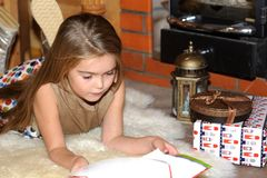 Child girl is reading in front of fireplace Stock Photos