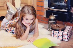 Child girl is reading in front of fireplace Stock Images
