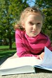 Child girl reading at the park Stock Images