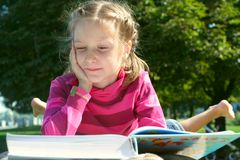 Child girl reading at the park Royalty Free Stock Photo