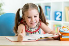 Child girl reading story from big book in nursery Royalty Free Stock Photo