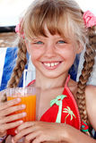 Child girl in red bikini drink  juice. Child girl in sunglasses and red bikini drink orange juice Royalty Free Stock Image