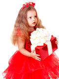 Child girl in red dress with gift box. Royalty Free Stock Images