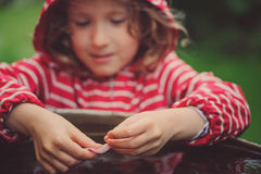 Child girl in red raincoat playing with water barrel, rainy day outdoor activities Stock Images