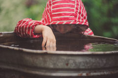 Child girl in red raincoat playing with water barrel, rainy day outdoor activities Royalty Free Stock Image