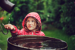 Child girl in red raincoat playing with water barrel, rainy day outdoor activities Royalty Free Stock Images