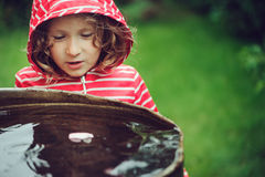 Child girl in red raincoat playing with water barrel, rainy day outdoor activities Stock Photo
