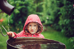 Child girl in red raincoat playing with water barrel in rainy summer garden. Water economy and nature care Royalty Free Stock Images