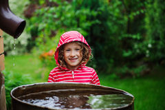 Child girl in red raincoat playing with water barrel in rainy summer garden. Water economy and nature care Royalty Free Stock Photos