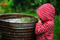 Child girl in red raincoat playing with water barrel in rainy summer garden. Water economy and nature care. Concept Stock Photography