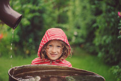 Child girl in red raincoat playing with water barrel in rainy summer garden. Water economy and nature care Stock Photography