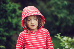 Child girl in red raincoat walking in rainy summer garden. Royalty Free Stock Photography