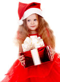 Child girl in red santa hat with gift box. Stock Photo