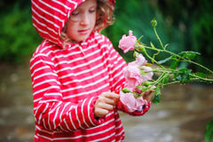 Child girl in red striped raincoat playing with wet roses in rainy summer garden. Nature care concept. Stock Image