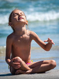 Child girl relaxing on beach yoga meditation Royalty Free Stock Photos