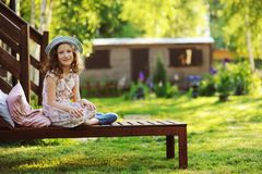 Child girl relaxing on sunbed in sunny garden. Enjoying summer vacations outdoor Stock Image