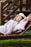 Child girl relaxing on sunbed in sunny garden, enjoying summer vacations. Outdoor Stock Photo