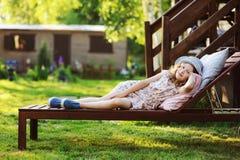 Child girl relaxing on sunbed in sunny garden. Enjoying summer vacations outdoor Stock Photos