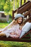 Child girl relaxing on sunbed in sunny garden. Enjoying summer vacations outdoor Stock Photography
