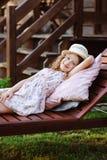 Child girl relaxing on sunbed in sunny garden. Enjoying summer vacations outdoor Stock Photo