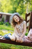 Child girl relaxing on sunbed in sunny garden. Enjoying summer vacations outdoor Royalty Free Stock Image