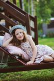 Child girl relaxing on sunbed in sunny garden Royalty Free Stock Image