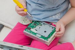 A child, a girl repairing a computer system unit. Baby girl, baby computer repair, system block screwdriver Royalty Free Stock Photos