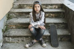 Girl with skateboard resting stock photography