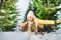 Child girl riding a sledge outdoors in snow Stock Photos