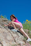 Child (Girl) rock climbing or hiking. Child girl rock climbing or hiking on a beautiful clear blue sky day Royalty Free Stock Photography