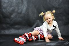 Child girl on the rollers fell royalty free stock photo