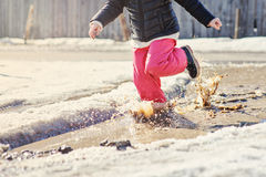 Child girl running in spring puddle with big splash stock photo