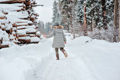 Child girl running on the walk in winter forest Stock Images