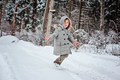 Child girl running in winter snowy forest Royalty Free Stock Photos