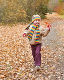 Child girl runs on a footpath in forest, autumn leaves background, fall season Royalty Free Stock Image