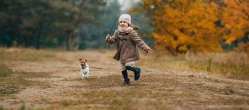 Child girl runs and plays with his dog during walk. royalty free stock photography