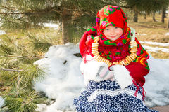 Child girl in Russian pavloposadskie folk scarf on head with floral print and with  bunch of bagels on background of snow. Stock Photo