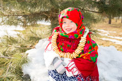 Child girl in Russian pavloposadskie folk scarf on head with floral print and with  bunch of bagels on background of snow. Stock Photography