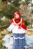 Child girl in Russian pavloposadskie folk scarf on head with floral print and with  bunch of bagels on background of snow. Stock Image