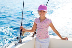 Child girl sailing in fishing boat holding rod. In blue sea Stock Image