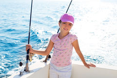 Child girl sailing in fishing boat holding rod. In blue sea Royalty Free Stock Photo