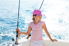 Child girl sailing in fishing boat holding rod. In blue sea Stock Images