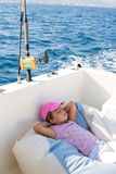 Child girl sailing relaxed on boat deck ejoying a nap Stock Image