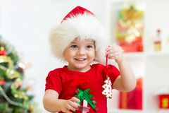 Child girl in Santa hat holding Christmas biscuits royalty free stock photography
