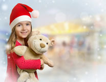 Child girl in santa hat with teddy bear. Background. Royalty Free Stock Image