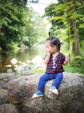 Child girl scared sitting on a rock stock photo