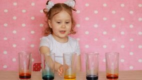 Child girl and science experiment. Children`s birthday. Tricks.Focuses. Entertainment for children. Preschool education. Multicolored drinks stock footage