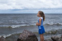Child girl on the sea before the storm, strong wind royalty free stock images