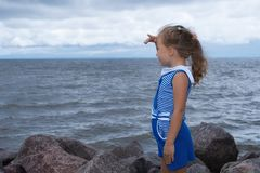 Child girl on the sea before the storm, strong wind stock photography