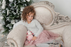 Child girl and sheep toy at Christmas time Stock Image